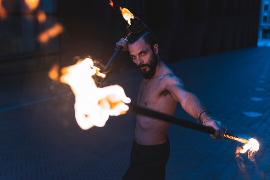 Hipster male juggling with fire staff on footpath at dusk