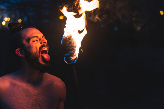 Male juggler performing with fire staff at night