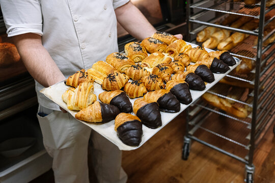 Male chef holding baking sheet filled with croissant in bakery kitchen