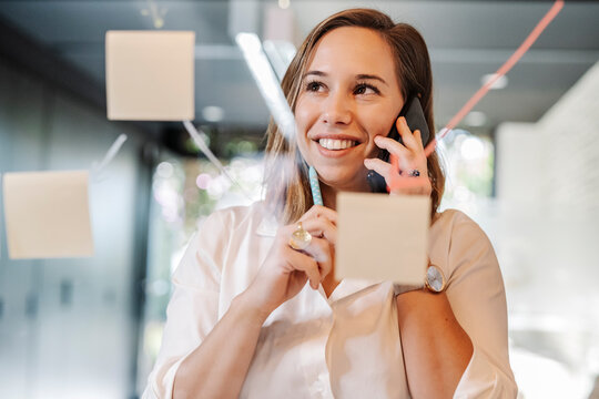 Close-up of smiling businesswoman talking over smart phone in office seen through glass wall