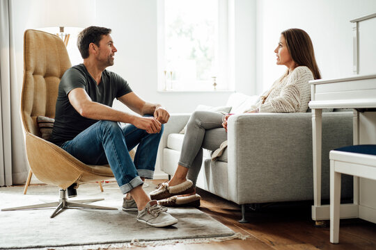 Mature couple talking while sitting in living room in apartment