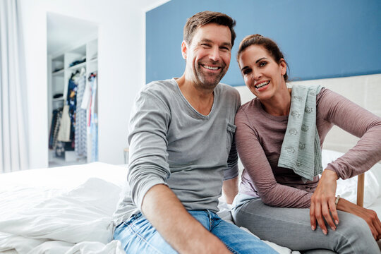 Happy mature couple sitting on bed in bedroom