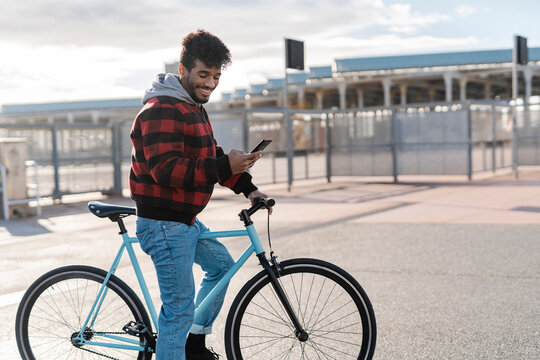 Young man wearing hooded shirt smiling while using mobile phone standing with bicycle on road