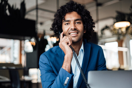 Smiling male professional talking on telephone while sitting with laptop at office