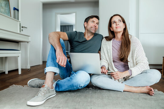 Mature couple with laptop and credit card contemplating while sitting in apartment
