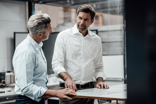 Business people discussing over plan while working at industry