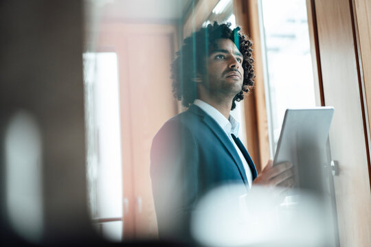 Thoughtful businessman looking away while standing with digital tablet at office