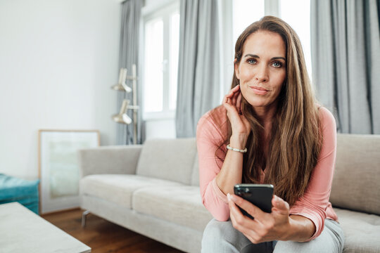 Mature woman with hand in hair holding mobile phone in living room at home