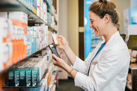 Happy pharmacist with smart phone checking medicine while working at pharmacy