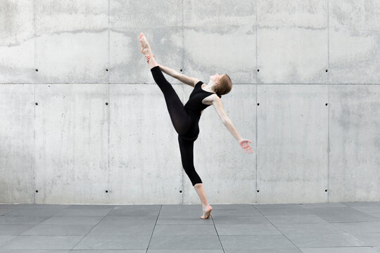 Dancer in black leotard dancing in front of concrete wall