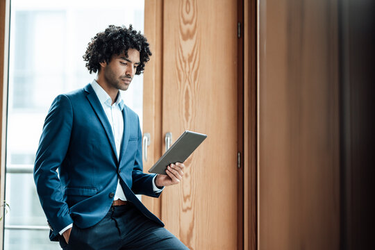 Confident young male professional using digital tablet at workplace