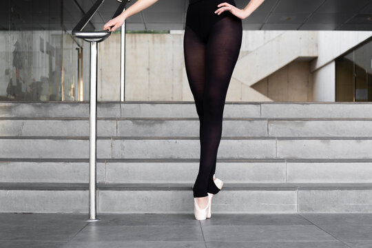 Legs of ballerina on tiptoes at railing in modern concrete building