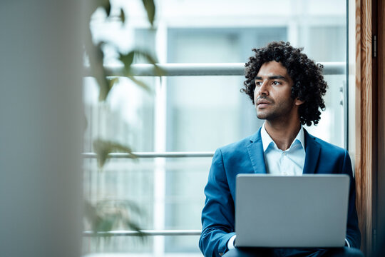 Thoughtful male professional looking away while sitting with laptop against window at workplace