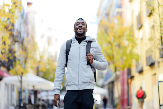 Man carrying backpack while walking in city
