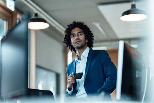 Thoughtful male entrepreneur holding coffee cup while sitting by computer monitors looking away in office