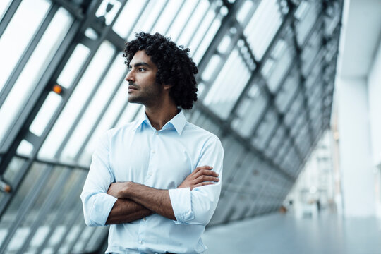 Thoughtful young male professional standing with arms crossed while looking away at workplace
