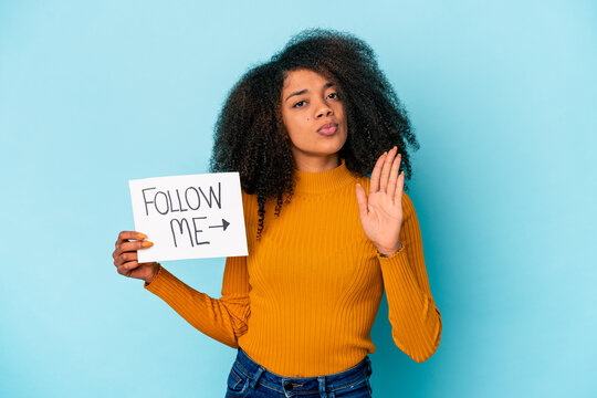 Young african american curly woman holding a follow me placard standing with outstretched hand showing stop sign, preventing you.