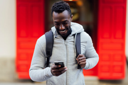 Young man with backpack smiling while using mobile phone standing outdoors