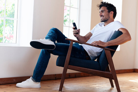 Smiling man using smart phone while resting on armchair at home