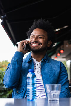 Smiling man with afro hair talking over mobile phone while sitting at sidewalk cafe
