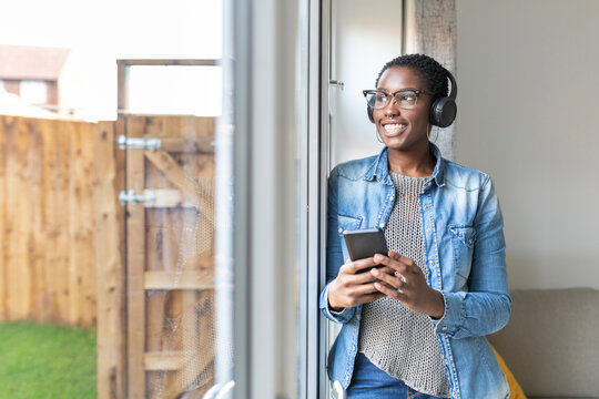 Smiling woman with headphones standing by window, holding smart phone