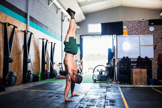 Shirtless male athlete practicing handstand on floor in health club