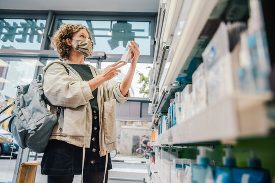 Female customer wearing protective face mask while checking medicine in chemist store