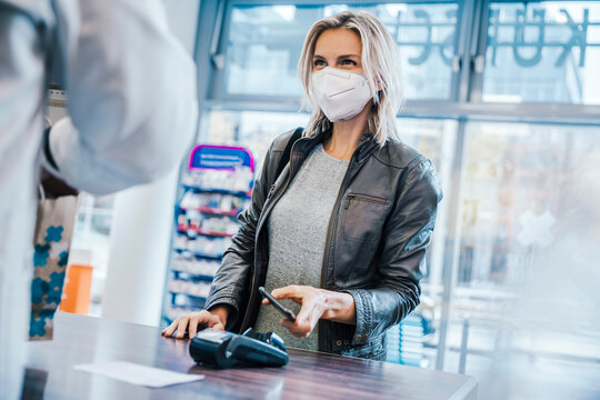 Female customer wearing face mask while making payment through smart phone at checkout counter in chemist shop