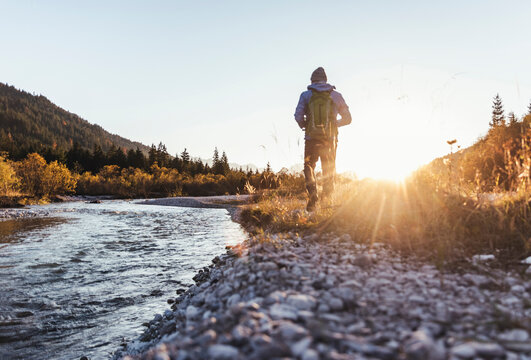 Male hiker with backpack walking on land by stream against clear sky at sunset
