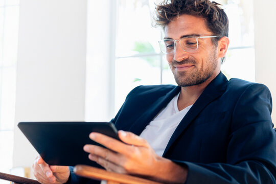 Smiling businessman using digital tablet while sitting at home