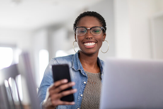 Smiling woman working using laptop and smart phone at home