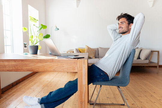 Smiling man with hands behind head relaxing while sitting on chair at home
