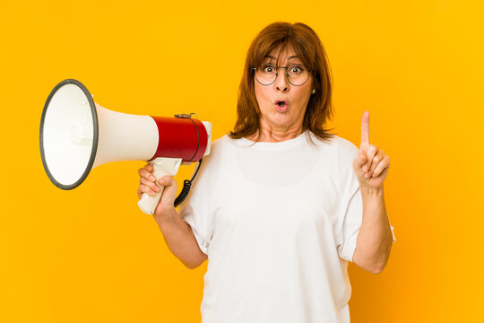Middle age caucasian woman holding a megaphone having some great idea, concept of creativity.