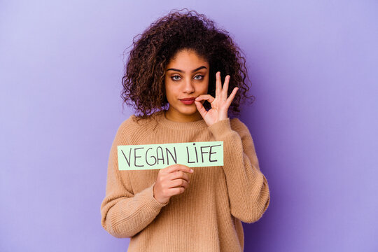Young African American woman holding a Vegan life placard isolated with fingers on lips keeping a secret.