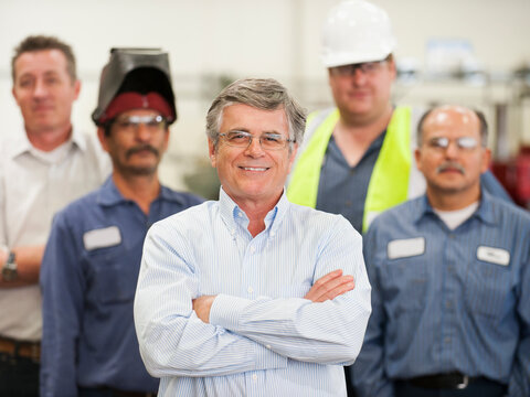Portrait of businessman and workers in factory