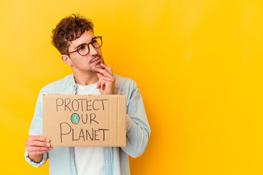 Young caucasian man holding a protect our planet placard isolated looking sideways with doubtful and skeptical expression.