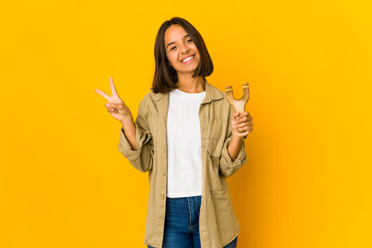 Young hispanic woman holding a slingshot joyful and carefree showing a peace symbol with fingers.