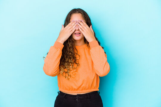 Young caucasian curly hair woman isolated afraid covering eyes with hands.
