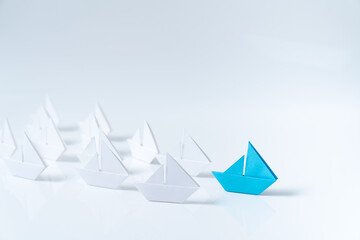Leadership or leader concept using a blue paper ship leading among white ships