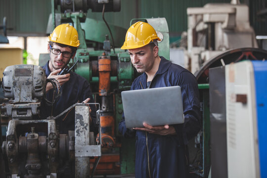 worker using digital laptop while supervising production at plant, copy space.  workers using machine equipment in factory
