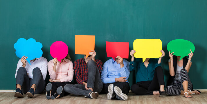 Group of six business people team sittiing together and holding colorful and different shapes of speech bubbles over their faces.