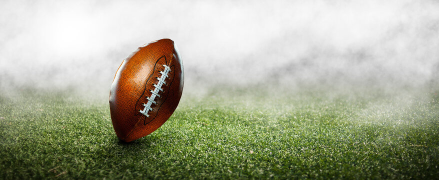 American football ball on the grass of a stadium