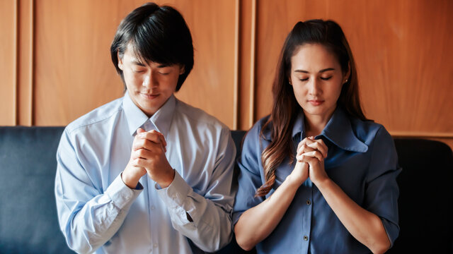 Asian Christian woman and man holding hands in praying for Jesus' blessings to show love and confession of their sins according to the Christian faith. Concept giving love faith..