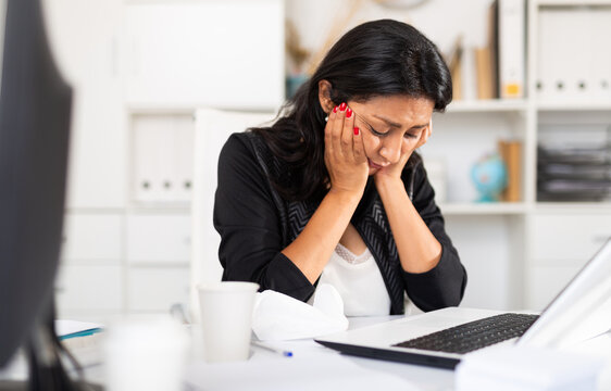 Portrait of disappointed crying latin american female office employee during work with laptop and documents