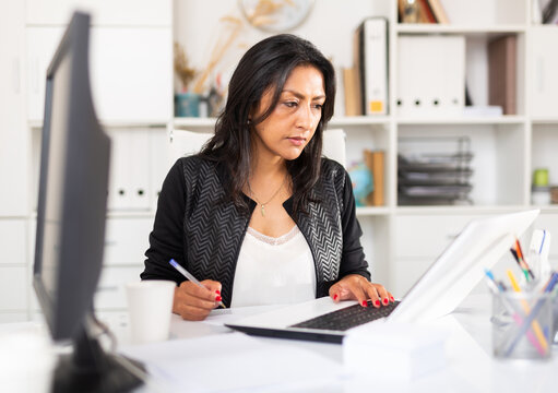 Focused hispanic business woman working alone on laptop in modern office ..