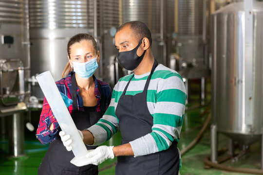 Man and woman in protective mask with beaker in a winery shop