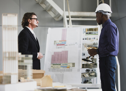 A man African American and Leadership caucasian architects standing presenting a structured work. On the board and a model of a house in the office.