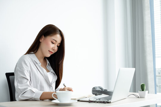 Asian female college students study online at home, enjoy extra lessons, watch videos, and take notes from a digital laptop, do homework by looking at the screen while sitting at a desk at home