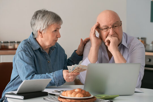 Stressed senior couple counting money at home