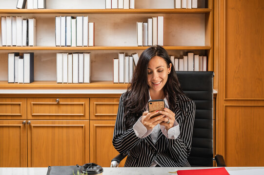 A young businesswoman or lawyer sitting at her desk in the office in front of a bookshelf smiling using a mobile phone device.